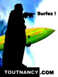 Stanislas se tient devant une vague, une planche de surf à la main